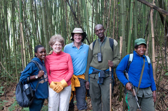 "Alexandra W. Logue, husband Ian Shrank, two guides, and the ""water buffalo"" guard ready to climb the mountain in Rwanda to see the gorillas"